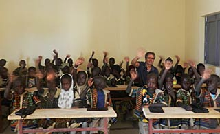Founder Barry Hoffner sits with students in their classroom at the school in Kakondji built by Caravan to Class