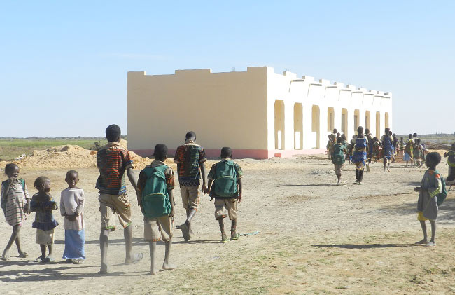 Image of students walking toward their new Bantam school built by Caravan to Class